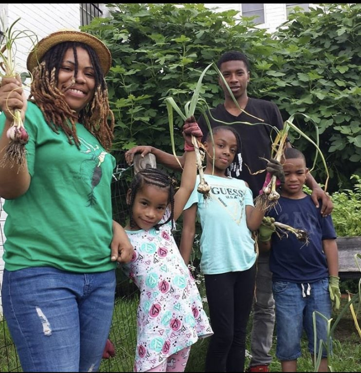 Queen gardening with the Beet Street Youth