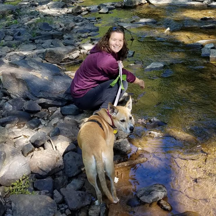 Picture of the author by a stream with her dog